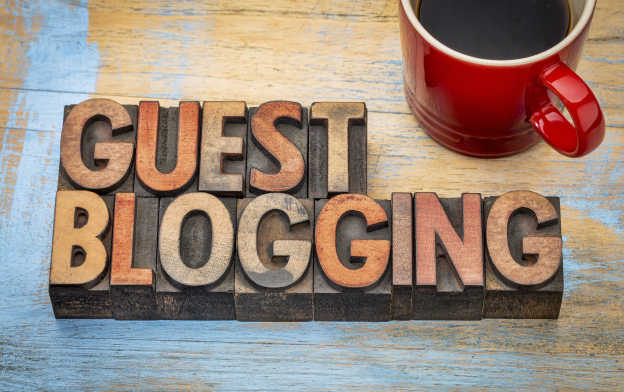 Wooden Letters forming the word Guest Blogging on a Wooden Table with a Red Cup of Coffee.